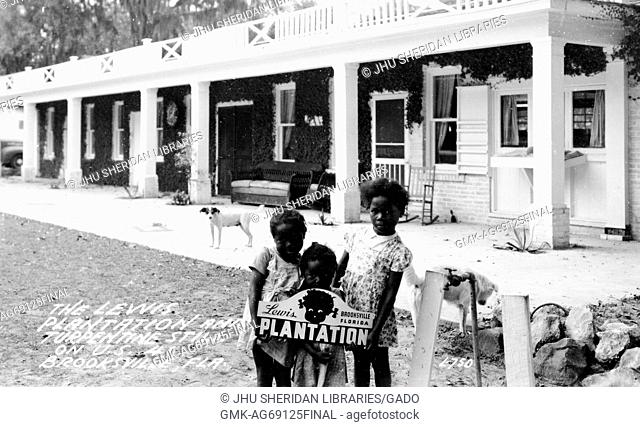 "Three young African American girls with neutral expressions stand outside with a """"Lewis Plantation"""" sign on the plantation, in front of housing"