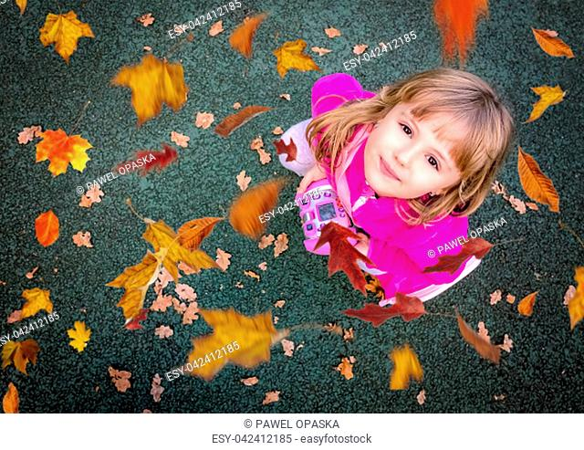 Portrait of a cute little Caucasian girl with looking up at the falling leaves in autumn