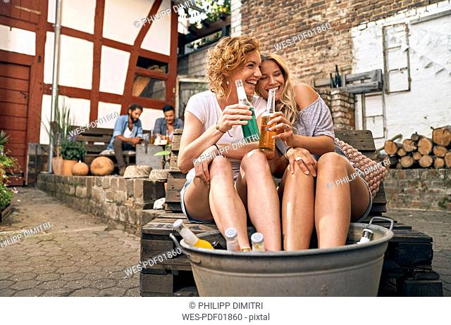 Friends relaxing in a backyard in summer, young women cooling their feet in a tub with drinks