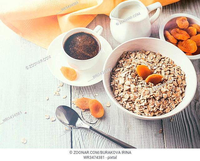 Breakfast from oatmeal with dried apricots and cup of black coffee on a white wooden table. Vintage style filter