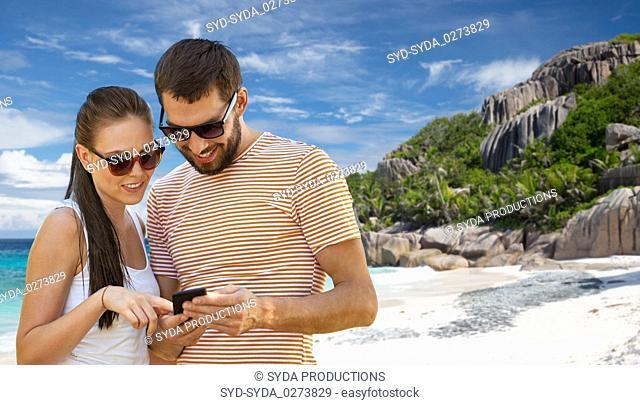 happy couple with smartphone on seychelles island