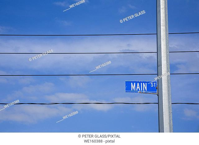 """""""""""""""""""""""Main Street"""""""" sign with cloudy sky and telephone wires behind it"""