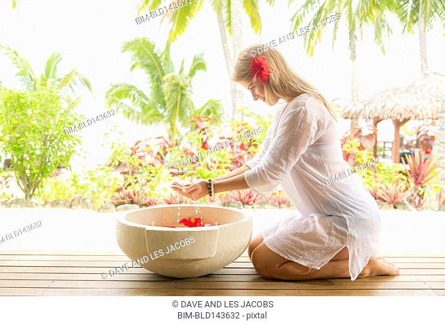 Caucasian woman soaking hands in spa bath