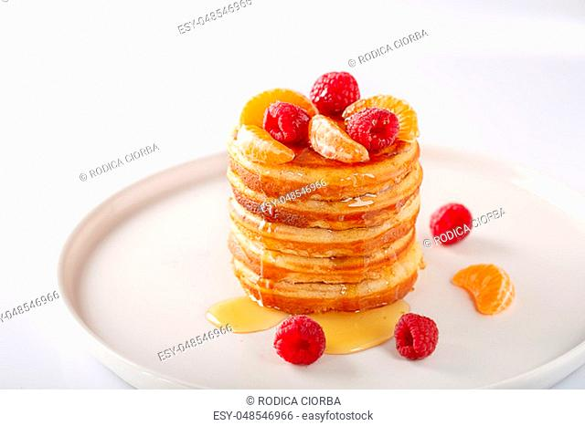 American Sweet homemade stack of pancakes or fritters with raspberry fruits and honey, delicious dessert for breakfast, on white background