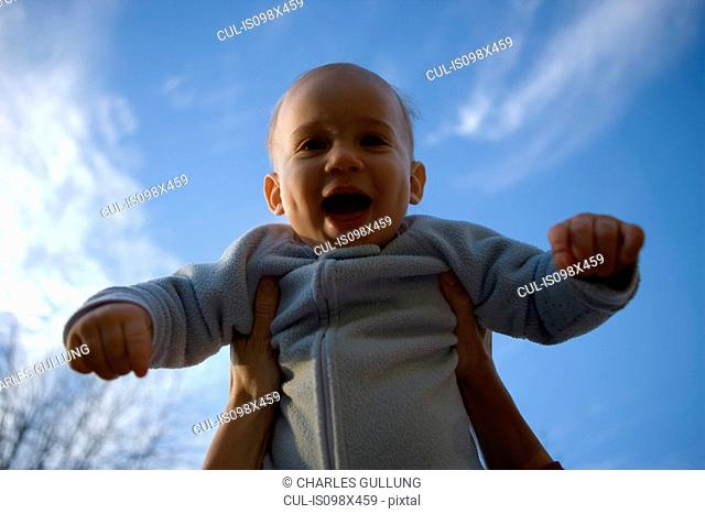 Parent holding baby boy mid air