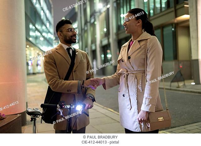 Business people with bicycle handshaking on urban sidewalk at night