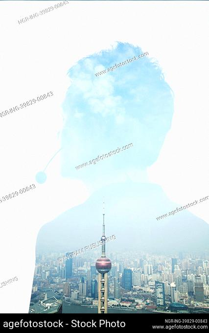 Double exposure of young businessman with headset and the skyline of Shanghai, China