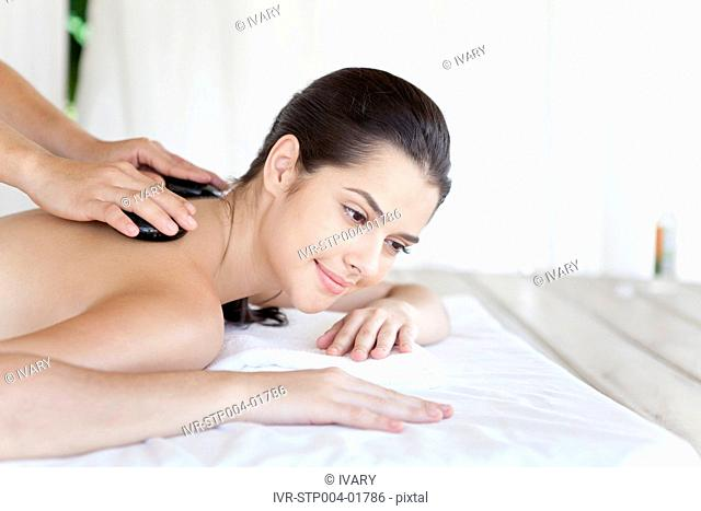 Young woman lying on her front at a spa treatment