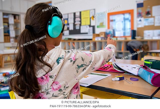 24 September 2019, Bavaria, Munich: A girl of a 2nd grade works in the primary school St. Konrad in the classroom with hearing protection on a worksheet