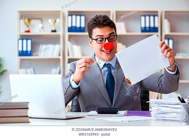 Clown businessman burning paper papers in the office