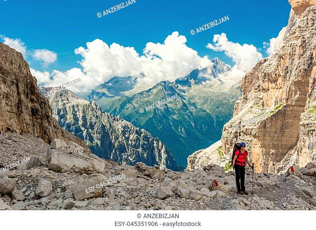 Female trekker walking along mountain valley. Trekking Brenta Dolomites, Sentiero delle Bocchette Alte
