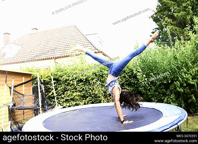 Young girl doing somersault on trampoline