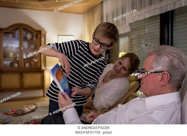Gift giving at Christmas eve, boy showing present to grandparents