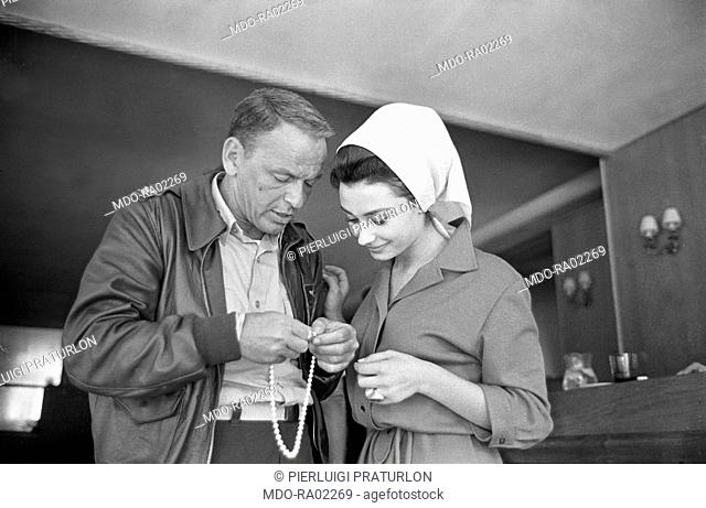 American actor Frank Sinatra and Italian actress Raffaella Carrà in Von Ryan's Express directed by Mark Hobson. Standing together they hold a pearl necklace