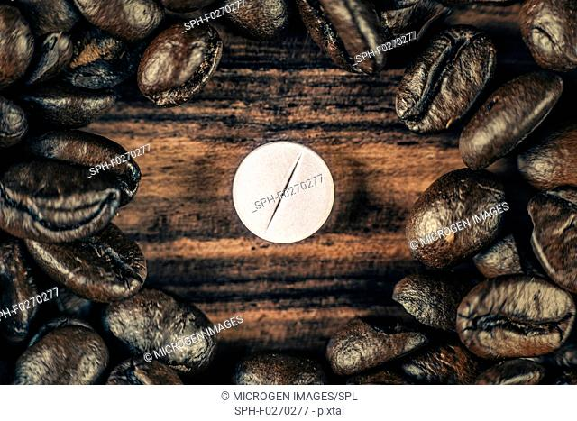 White caffeine pill surrounded by roasted coffee beans on wooden background