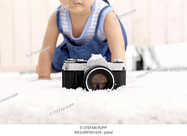 Camera lying on carpet while baby girl crawling in the background