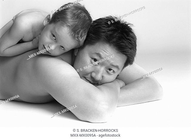 Asian man lying down with boy on back