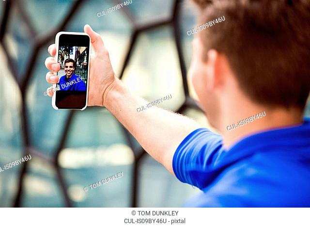 Young man taking selfie in front of glass wall, London, UK