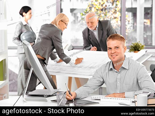 Architects busy at work, young designer in focus sitting at desk using drawing pad, smiling at camera