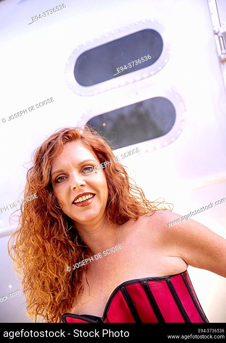 A 41 year old redheaded woman wearing a red bustier and black leather pants