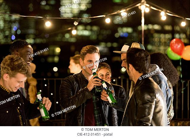 Young men drinking beer at rooftop party