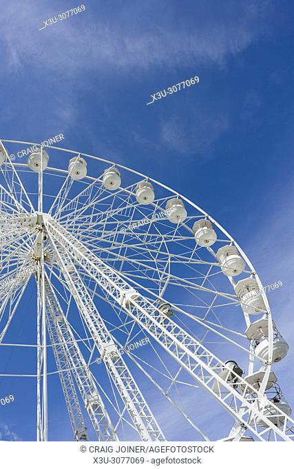 A Ferris wheel, or big wheel, at a fairground against a blue sky