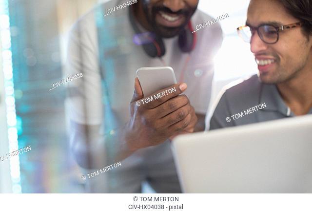 Smiling creative businessmen using smart phone