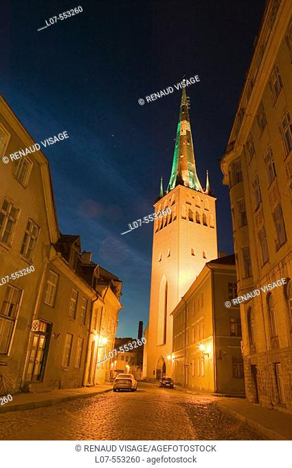 Cobble stone street and St Olaf Church in Old Town at night. Tallinn. Estonia