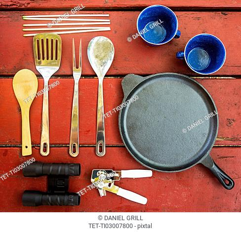 Skillet, cups and cooking utensils on picnic table