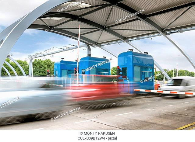 Cars travelling through toll booth at bridge