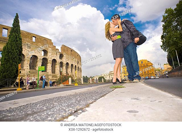 Couple kissing on the street before the Roman Colosseum in Rome Italy