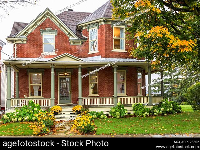 Old 1900 Victorian Queen Anne revival style house facade with red brick cladding, green and cream trim in autumn, Quebec, Canada