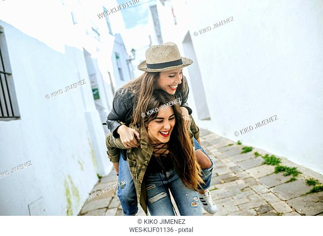 Happy young woman giving friend a piggyback ride