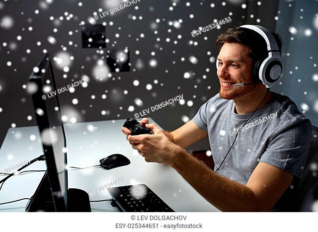 technology, gaming, entertainment, let's play and people concept - happy man in headset with controller gamepad playing computer game at home and streaming...