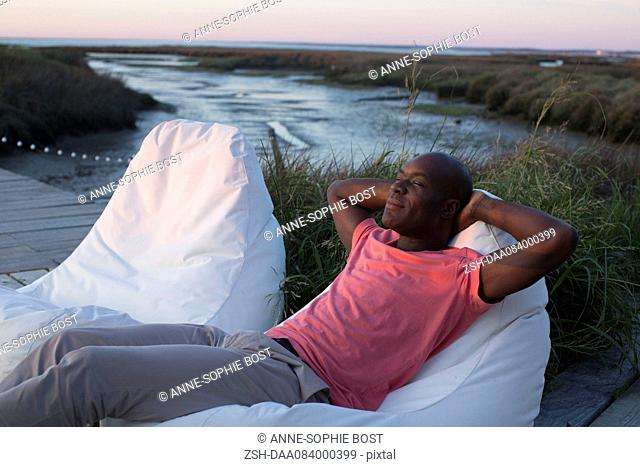 Man relaxing at water's edge