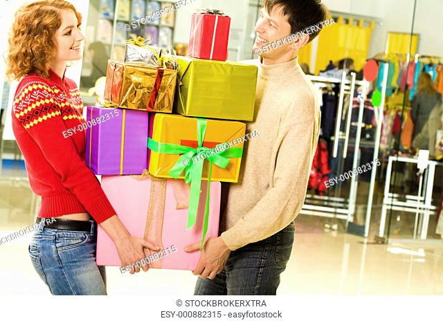 Portrait of shopaholics holding heap of presents and wondering what to do next