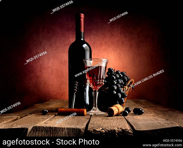 Grape in basket with wine on a wooden table
