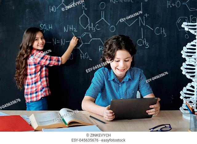 Enjoying educational process. Brainy gifted intelligent teenagers sitting at school and enjoying chemistry class while making notes on the blackboard and using...