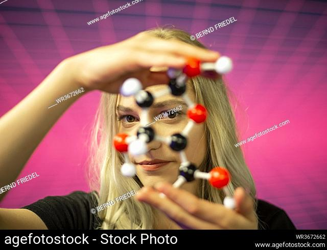 Close-up of young female scientist holding molecule model against grid pattern