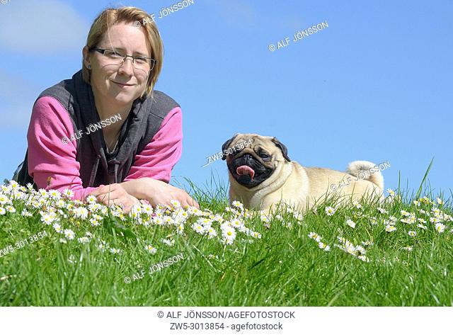 Young woman lying with a pug dog on a green and with a blue sky in Ystad, Scania, Sweden