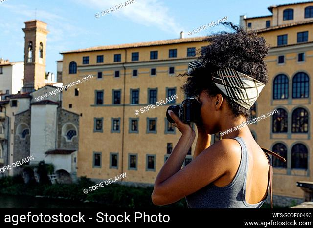 Young woman taking photo with camera, Florence, Italy