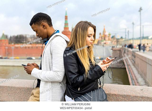 Russia, Moscow, multiracial couple using smartphones in the city