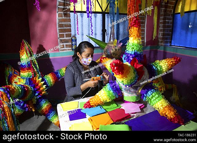 ACOLMAN, MEXICO - MARCH 7, 2021: A woman manufactures the traditional Mexican pinata, made from a clay pot wrapped in multicolored paper