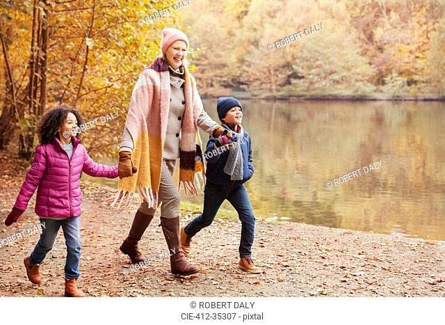 Grandmother holding hands with grandchildren walking along pond in autumn park