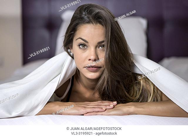 Young charming woman with long silky hair lying under white blanket on bed and looking at camera