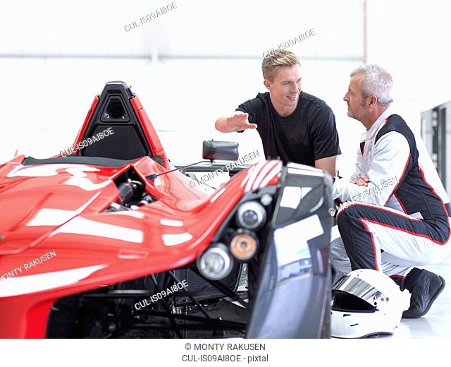 Racing car driver and engineer with supercar in sports car factory