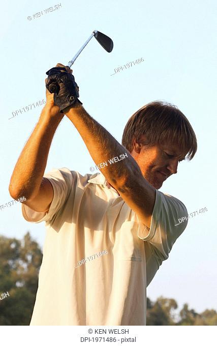 man in mid-swing with a golf club, toremolinos malaga province spain
