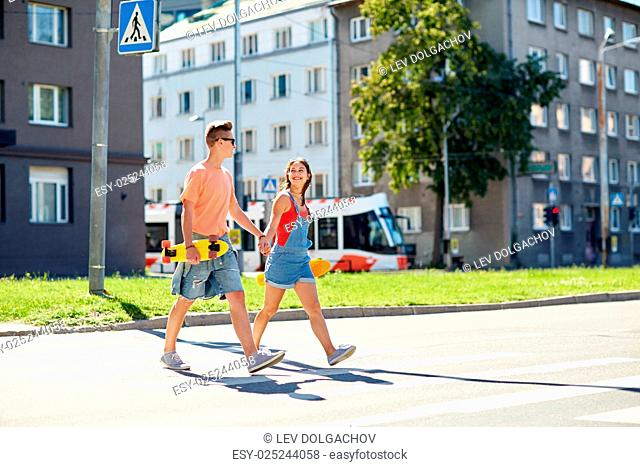 summer holidays, extreme sport and people concept - happy teenage couple with short modern cruiser skateboards crossing city crosswalk