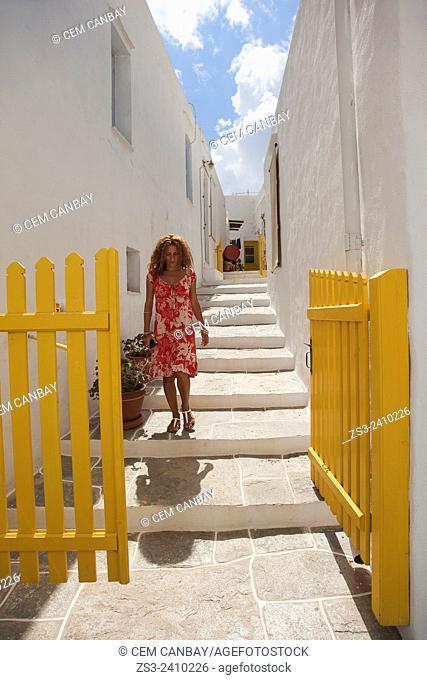 Woman walking in the alleys of town, Apollonia village, Sifnos, Cyclades Islands, Greek Islands, Greece, Turkey