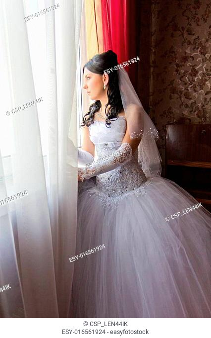 Beautiful young bride standing beside a window
